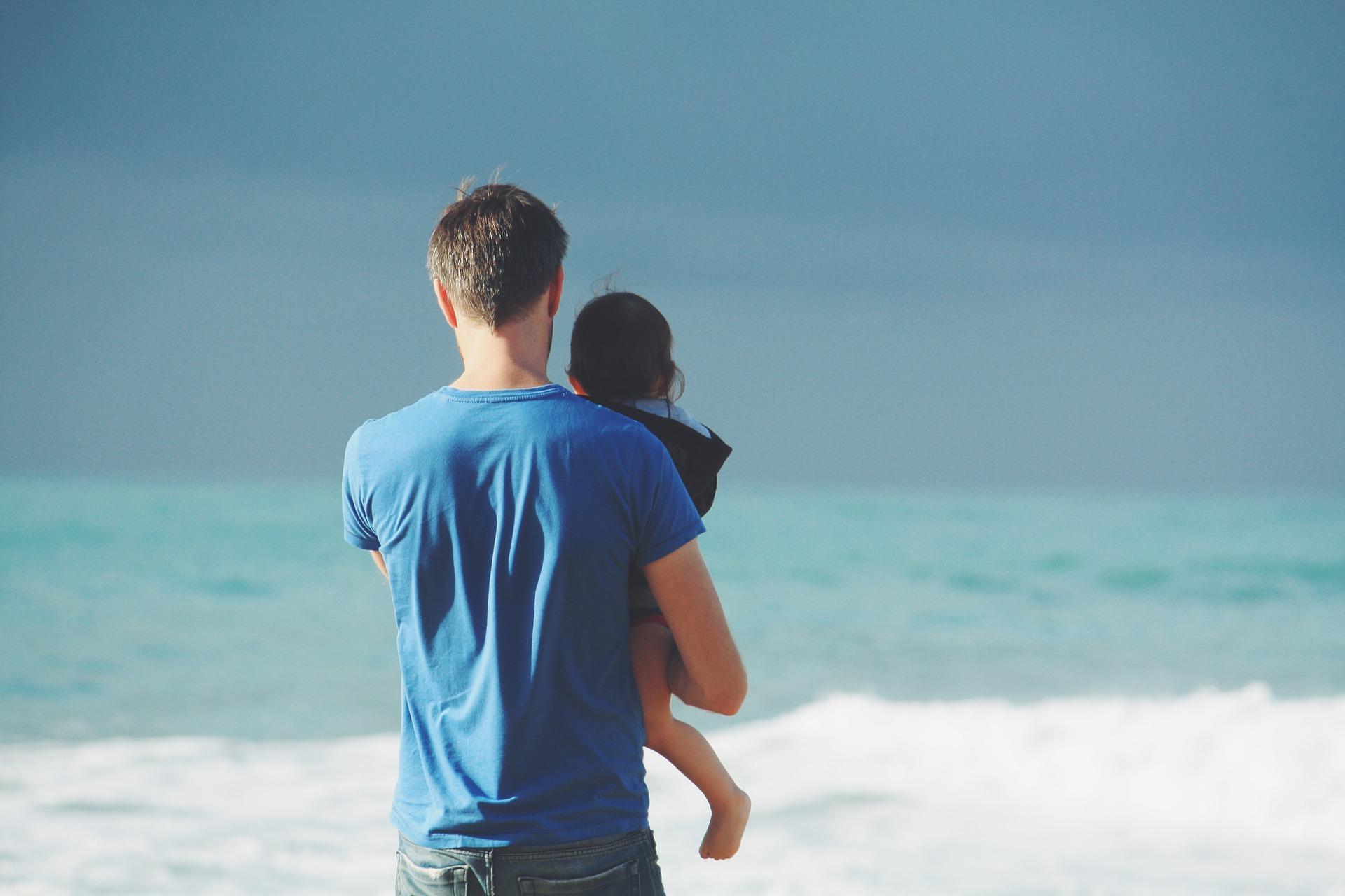 mand med barn ved strand
